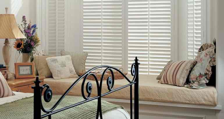 White shutters in a modern bedroom bay window.