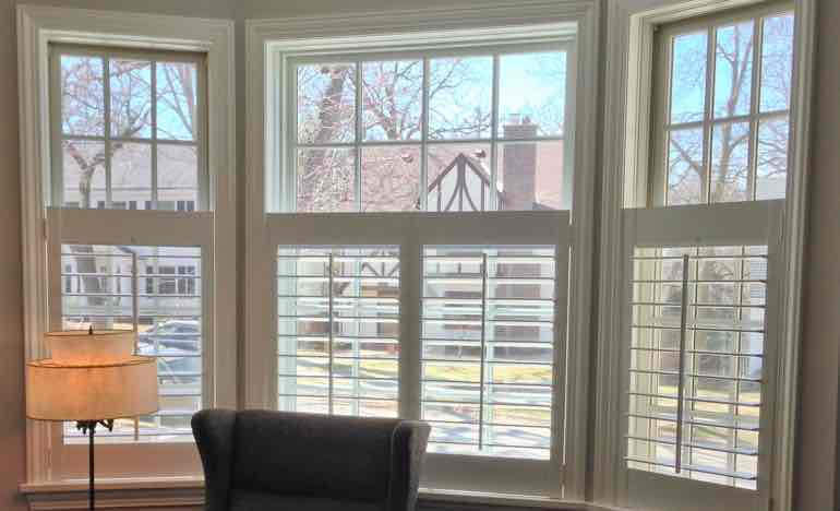 Half-length plantation shutters in family room bay window.