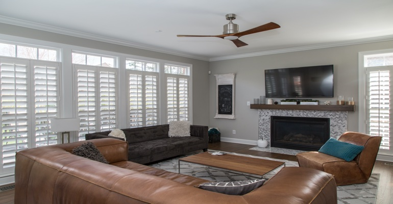 Shutters in a living room with a tv