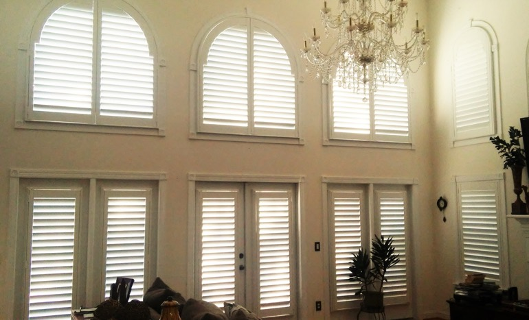 Entertainment room in open concept Philadelphia home with plantation shutters on high ceiling windows.