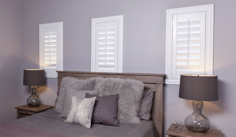 White plantation shutters in Philadelphia bedroom windows.