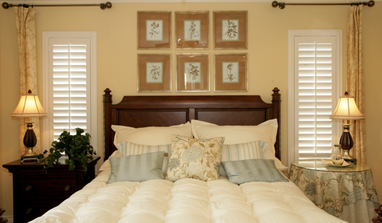 Tall plantation shutters framing bed in a bedroom in Philadelphia