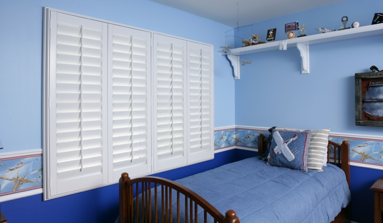 Large plantation shutters covering window in blue kids bedroom in Philadelphia